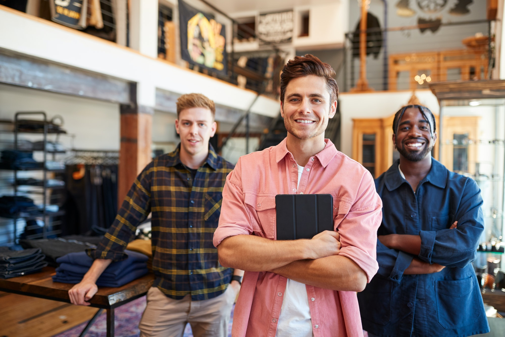 Portrait Of Smiling Multi-Cultural Male Sales Team In Fashion Store In Front Of Clothing Display